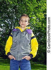 Cute  boy in a yellow hoodie against green trees background