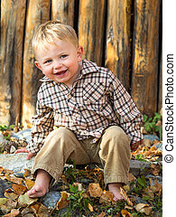 Cute boy in autumn leaves