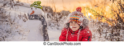 Cute boy in red winter clothes builds a snowman. Winter Fun Outdoor Concept BANNER, LONG FORMAT