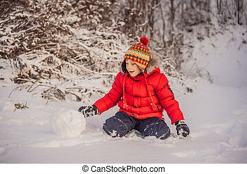 Cute boy in red winter clothes builds a snowman. Winter Fun Outdoor Concept