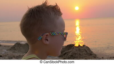 Cute boy in sunglasses on the beach at sunset