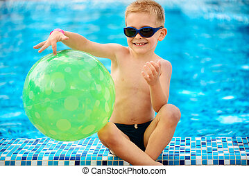 Cute boy in sunglasses sitting at pool