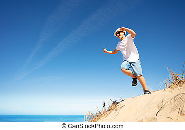 Cute boy in white jump from sand dune on a beach