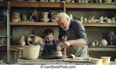 Cute boy is molding clay on throwing wheel while his caring...