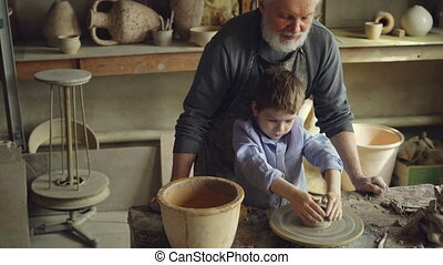 Cute boy is wetting hands in bowl and watering clay figure...