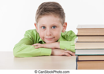 cute boy leaning on table and smiling. handsome little schoolboy studying on white background