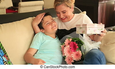 Cute boy offering gift to her mother