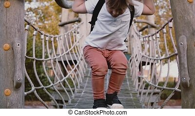 Cute boy on adventure park ropes course. Thoughtful male kid walks on rope bridge, obstacles. Playground. Slow motion.