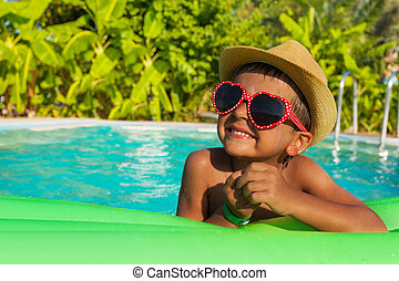 Cute boy on green airbed in the swimming pool