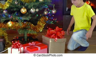cute boy open his present at christmas tree