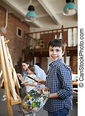 Cute Boy Painting at Easel