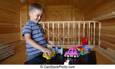 Cute boy plaing with toy car