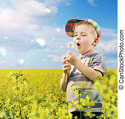 Cute boy playing dandelions on the meadow