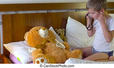 cute boy playing doctar with teddy bear - little boy playing...