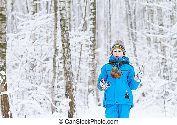 Cute boy playing in a winter forest