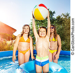 Cute boy playing in swimming pool with two girls