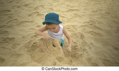 Cute boy playing in the sand on tropical beach at summer.