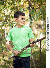 Cute boy playing in the thicket with a stick
