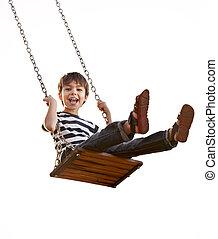 Cute boy playing on swing