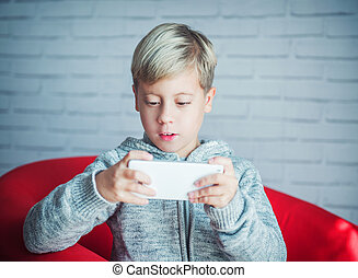 Cute boy playing with a smartphone