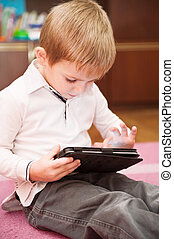 Cute boy playing with tablet