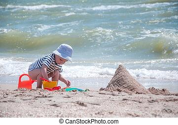 cute boy plays a bucket on the beach