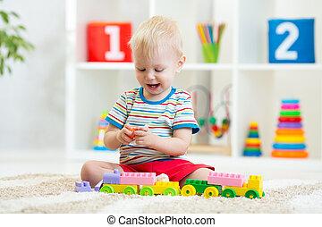 cute boy plays with building blocks toys in nursery
