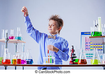 Cute boy posing with variety of reagents in lab