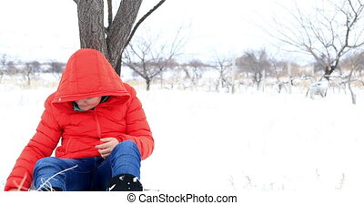 Cute boy relaxing in the winter park