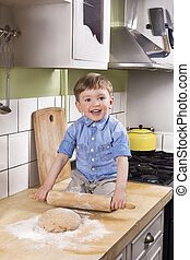 Cute boy rolling dough