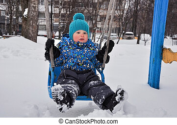 cute boy shakes on a swing in the winter