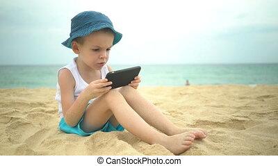 Cute boy sitting at sandy beach and using smartphone app