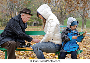 Cute boy sitting on a park bench holding a tablet computer while his mother and grandfather play chess
