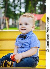 cute boy sitting on bench