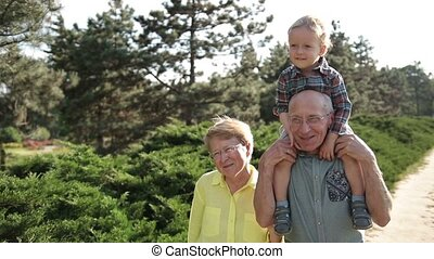 Cute boy sitting on grandfather's shoulder outdoor