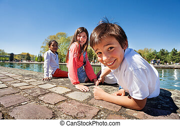 Cute boy sitting on the embankment with friends