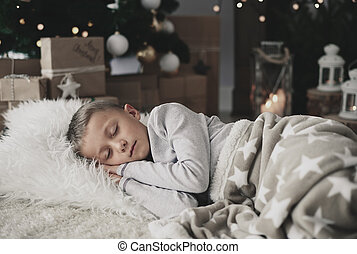 Cute boy sleeping on rug