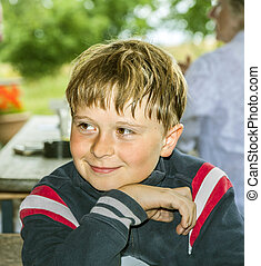 boy smiles and has fun sitting at the table