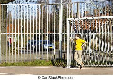 Cute boy staying in gate on the playground