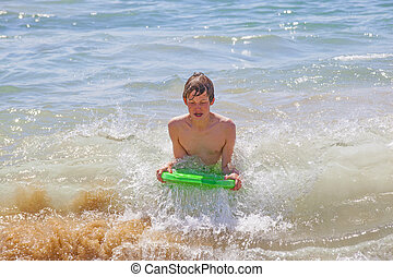 cute boy surfing in the waves