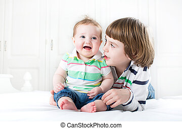 Cute boy talking to his baby sister