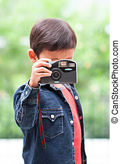 boy using compact camera. - Cute boy using compact camera.