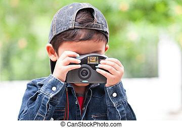 Cute boy using compact camera.