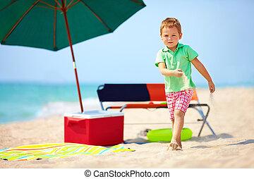 cute boy walking the sea beach