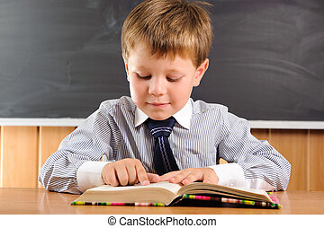 Cute boy with books at the desk - Cute elementary aged boy...