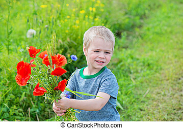 Cute boy with bunch of red poppies