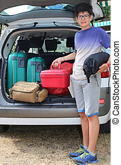 boy with glasses loaded the trunk of the car before leaving