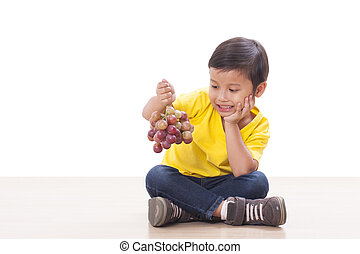 Cute boy with grapes