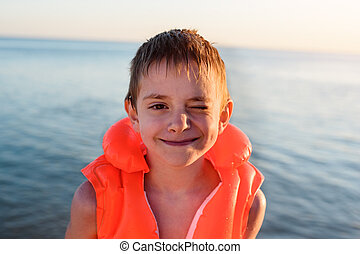 Cute boy with happy smile in inflatable swimming against the sea.