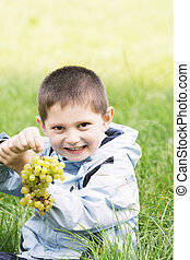 Cute boy with heavy bunch of grapes